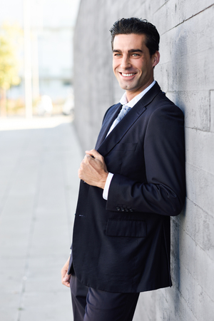 young businessman: Young businessman wearing blue suit and tie in urban background. Man with formal clothes in the street. Blue eyes guy smiling. Stock Photo