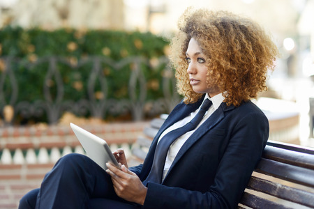 Beautiful black curly hair african woman using tablet computer on an urban bench. Businesswoman wearing suit with trousers and tie, afro hairstyle. Фото со стока