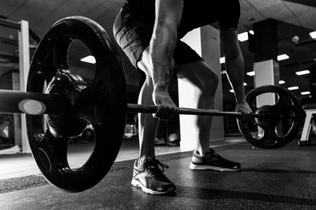 Primo piano di allenamento weightlift in palestra con bilanciere. Uomo che indossa abiti sportivi.