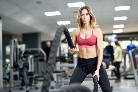 rope: Woman with battle ropes exercise in the fitness gym. Young female wearing sportswear.