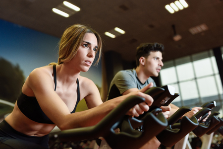 cardio workout: Attractive woman and man biking in the gym, exercising legs doing cardio workout cycling bikes. Couple in a spinning class wearing sportswear.
