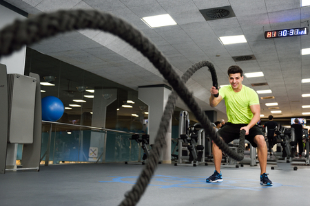 battle cross: Man with battle ropes exercise in the fitness gym. Young male wearing sportswear.
