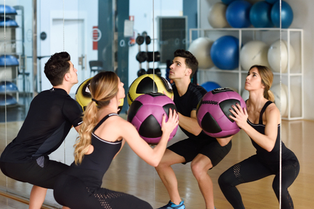 indoor: Man and Woman lifting fitballs in the gym. Young people wearing sportswear clothes in front of a mirror.