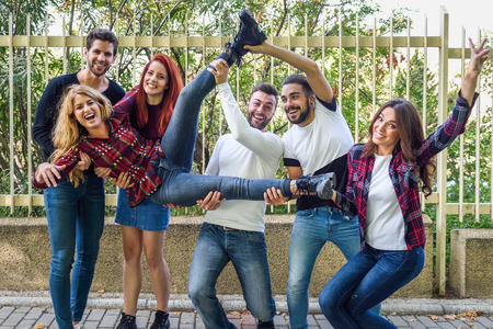 girls youth: Group portrait of boys and girls with colorful fashionable clothes holding friend. Urban style people having fun - Concepts about youth and togetherness.