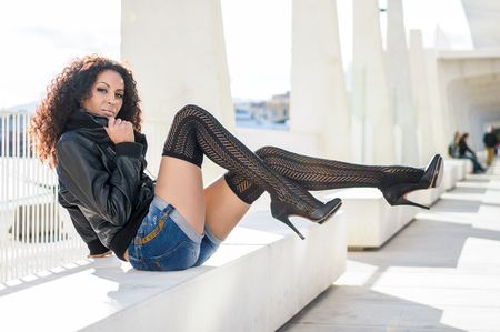 Young black woman, afro hairstyle, in urban background moving her long legs. Female wearing casual clothes. Girl with leather jacket and denim shorts. photo