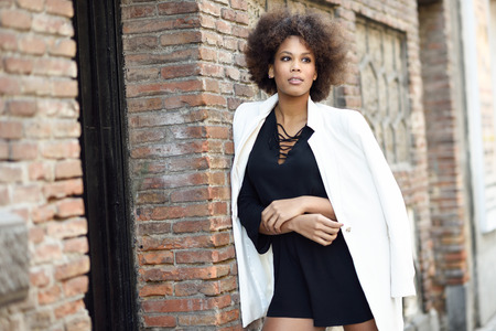 style woman: Young black woman with afro hairstyle standing in urban background. Mixed girl wearing white jacket and black dress posing near a brick wall