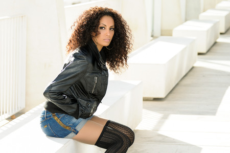 Black female, afro hairstyle, in urban background. Woman wearing denim jear shorts and leather jacket.