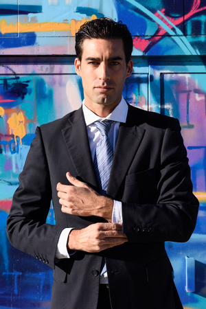 young businessman: Businessman wearing blue suit and tie in urban graffiti background. Man with formal clothes in the street. Blue eyes guy.