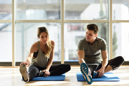 man gym: Young woman and man working out indoors. Two people streching their legs on the floor of a gym.