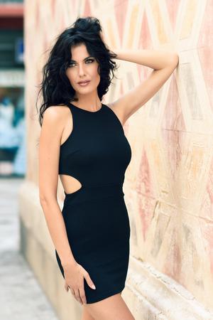 belle brune: Brunette femme portant robe noire séduisante dans la rue. Jeune fille avec bouclés coiffure debout en arrière-plan urbain
