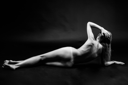 woman naked body: Young naked woman posing on black background. Perfect skin. Black and white photograph