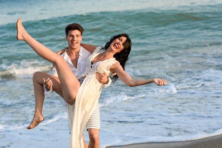Joven pareja feliz caminar en una hermosa playa. Hombre divertido que lleva una mujer en sus brazos. Las personas que usan ropa casual.