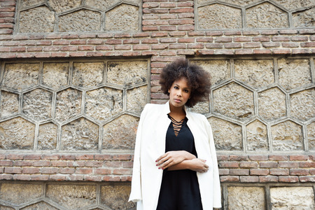blazer: Young black woman with afro hairstyle standing in urban background. Mixed girl wearing white blazer jacket and black dress posing near a brick wall. Fashion model. Stock Photo