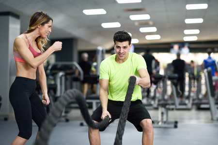 Female personal trainer motivating young man with battle ropes exercise in the fitness gym.