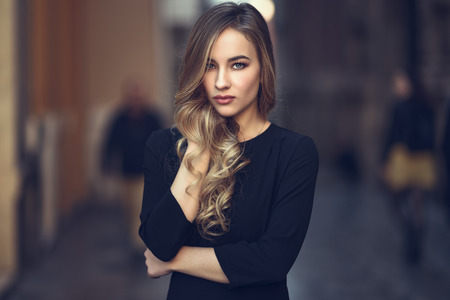 ojos azules: Mujer rubia en segundo plano urbano. Hermosa joven llevaba negro elegante vestido de pie en la calle. Hembra bonita rusa con corte de pelo largo pelo ondulado y ojos azules.