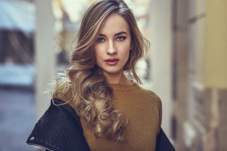 都市の背景に金髪の女性。通りで身に着けている黒い革のジャケットとミニのスカート立っている美しい少女。長いウェーブのかかった髪の髪型と 写真素材