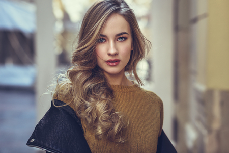 Blonde woman in urban background. Beautiful young girl wearing black leather jacket and mini skirt standing in the street. Pretty russian female with long wavy hair hairstyle and blue eyes. Stock Photo