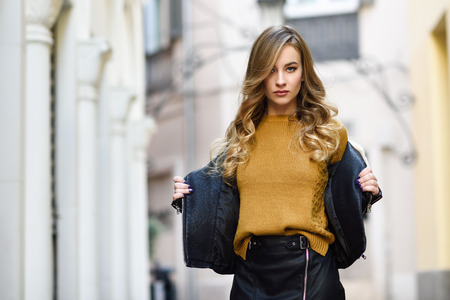 Blonde woman in urban background. Beautiful young girl wearing black leather jacket and mini skirt standing in the street. Pretty russian female with long wavy hair hairstyle and blue eyes. Imagens