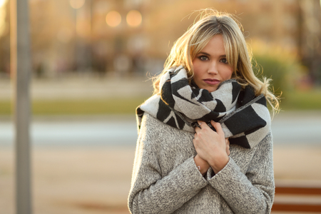 blonde woman: Attractive blonde woman in urban background with sun backlight. Young girl wearing winter coat and scarf standing in the street. Pretty female with straight hair hairstyle and blue eyes. Stock Photo