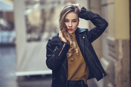 Blonde woman in urban background. Beautiful young girl wearing black leather jacket and mini skirt standing in the street. Pretty russian female with long wavy hair hairstyle and blue eyes. Standard-Bild