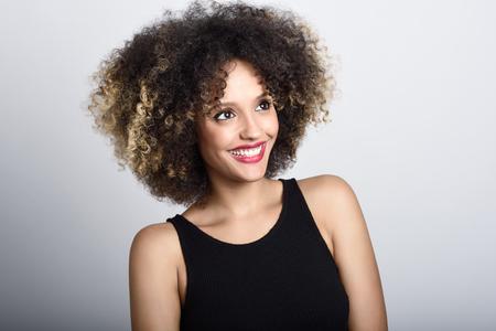 black girl: Junge schwarze Frau mit Afro-Frisur lachen. Mädchen tragen schwarze Kleidung. Studio gedreht.
