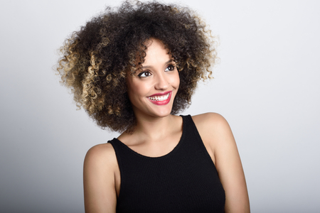 BLACK GIRL: Young black woman with afro hairstyle laughing. Girl wearing black clothes. Studio shot.
