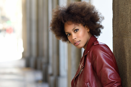 style woman: Young black female with afro hairstyle standing in an urban street. Mixed woman wearing red leather jacket and white dress with city background.