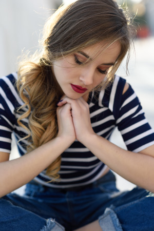 Blonde woman, model of fashion, sitting on a bench in urban background with eyes closed. Thoughtful young girl wearing striped t-shirt and blue jeans in the street. Pretty russian female with pigtail. Stock Photo