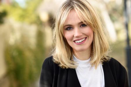 Belle femme blonde souriante en arrière-plan urbain. Jeune fille portant la veste blazer noir debout dans la rue. Jolie femme avec coiffure cheveux raides et les yeux bleus.