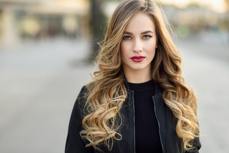 blonde: Close-up portrait of young blonde girl with beautiful blue eyes wearing black jacket outdoors. Pretty russian female with long wavy hair hairstyle. Woman in urban background. Stock Photo