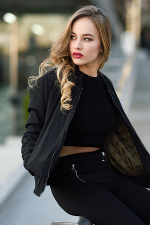 Young blonde girl with beautiful blue eyes wearing black jacket and trousers outdoors. Pretty russian female with long wavy hair hairstyle. Woman in urban background.