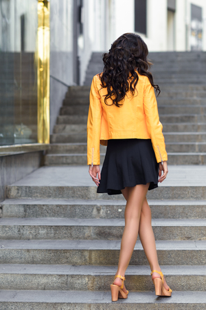Young brunette woman, model of fashion, wearing orange modern jacket and blue skirt. Pretty caucasian girl with long wavy hairstyle. Female in urban background with beautiful legs. Rear view.
