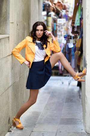 female legs: Young brunette woman, model of fashion, wearing orange modern jacket and blue skirt. Pretty caucasian girl with long wavy hairstyle. Female with beautiful legs in urban background. Stock Photo