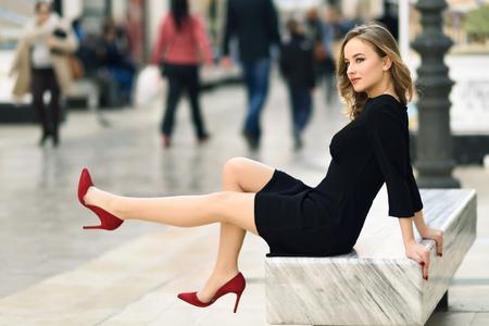 Grappige blonde vrouw met mooie benen in stedelijke achtergrond. Mooi meisje dragen zwarte elegante jurk en rode hoge hakken zittend op een bankje in de straat. Pretty Russische vrouw met lang golvend haar kapsel en blauwe ogen.