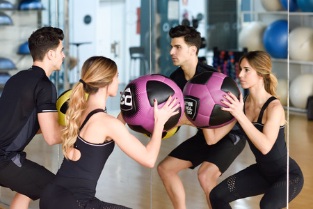 fitball: Man and Woman lifting fitballs in the gym. Young people wearing sportswear clothes in front of a mirror.
