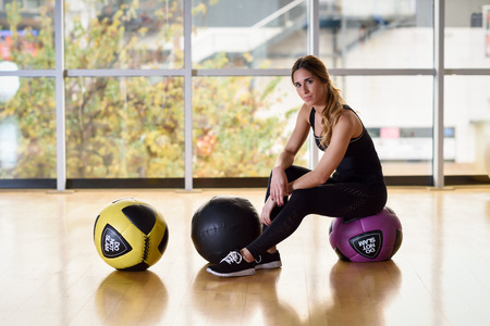 fitball: Woman sitting with fitballs in the gym. Young female wearing sportswear clothes.
