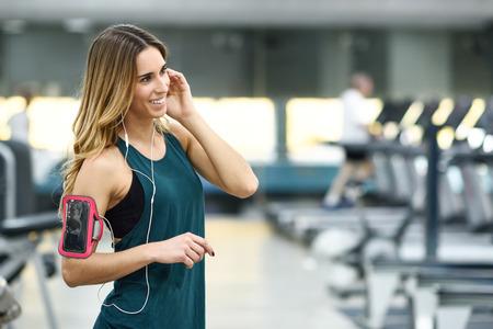 joven mujer utilizando teléfono inteligente de pie en el gimnasio antes de la formación. Hermosa niña sonriente. Foto de archivo