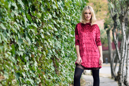 pretty eyes: Beautiful blonde woman in urban background. Young girl wearing red dress and tights standing in the street. Pretty female with straight hairstyle and blue eyes.