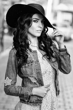 fashion dress: Young brunette woman, model of fashion, wearing denim jacket, hat, and dress. Pretty caucasian girl with long wavy hairstyle in urban background. Black and white.