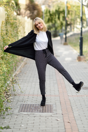 Funny blonde woman smiling in urban background. Young girl wearing black blazer jacket and striped trousers standing in the street. Pretty female with straight hair hairstyle and blue eyes.