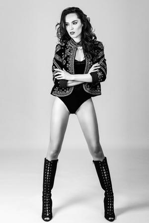 chica atractiva, modelo de la manera, el uso de chaqueta moderna, botas altas y lencería negro. Mujer con el peinado ondulado largo. Foto de estudio.
