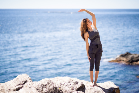 asana: Young woman doing yoga in the beach. Female wearing sport clothes with defocused sea background.