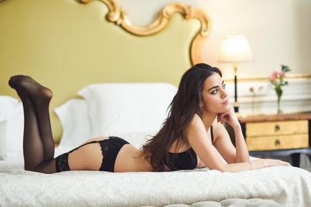 ベッドでポーズのランジェリーでセクシーな若い女性。彼女の寝室で黒い下着ブルネットの少女