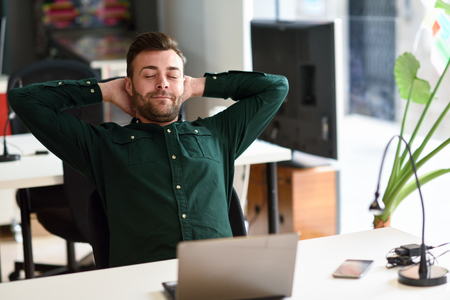 business casual: Young man studying with laptop computer on white desk. Attractive guy with beard wearing casual clothes taking a break.