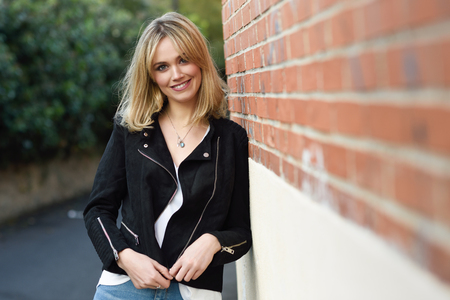 Attractive blonde woman smiling in urban background. Young girl wearing black zipper jacket and blue jeans trousers standing in the street. Pretty female with straight hair hairstyle and blue eyes on brick wall. Stock Photo