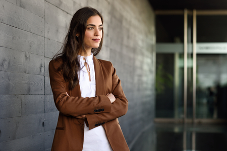 Young businesswoman standing outside of office building. Beautiful woman wearing formal wear. Young girl with brown jacket and trousers. Stock Photo