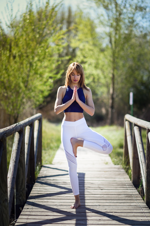 tree position: Young woman doing yoga in nature. Female wearing sport clothes in tree figure. Stock Photo