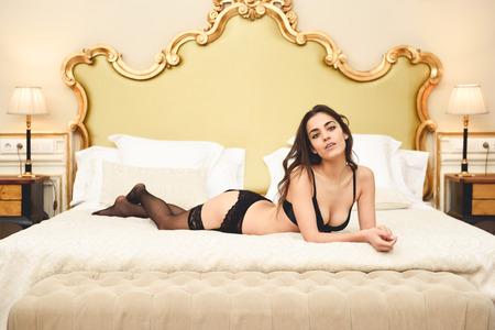 침대에 포즈 란제리 섹시 한 젊은 여자. 그녀의 침실에 검은 속옷에 갈색 머리 소녀 스톡 콘텐츠