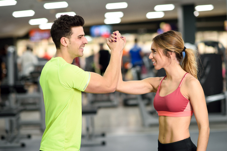 Smiling young man and woman doing high five in gym. Couple wearing sportswear