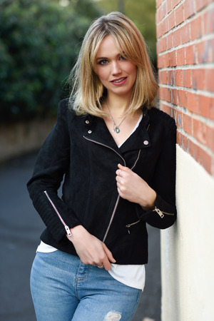 Attractive blonde woman in urban background. Young girl wearing black zipper jacket and blue jeans trousers standing in the street. Pretty female with straight hair hairstyle and blue eyes on brick wall. Stock Photo